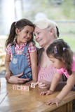 Loving grandmother teaching calculation to granddaughters at table in house Royalty Free Stock Image