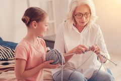 Loving grandmother teaching little girl how to knit. Imparting my knowledge. Selective focus on a mindful senior lady sitting next to her preteen granddaughter stock photo