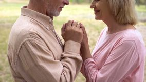 Loving grandparents looking each other, holding hands, caring spouse support. Stock photo royalty free stock photo