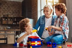 Loving granny chatting with grandsons while they playing Stock Photo