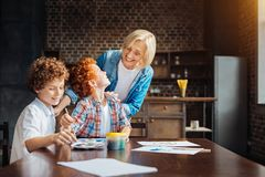 Loving granny looking and grandchildren painting together Stock Image