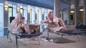 Aging couple enjoying leisure in hotel near pool stock footage