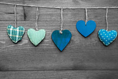 Loving Greeting Card With Turquoise Hearts. Wooden Background With Turquoise Hearts Hanging In A Row. Black And White Style With Colored Hot Spots. Copy Space Royalty Free Stock Photography