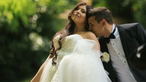 Loving groom kisses shoulder of his charming bride in sunny summer park. Outdoor wedding shot with slow-motion stock video