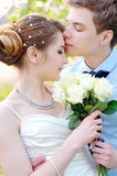 Loving groom kissing bride's forehead on wedding walk Stock Images
