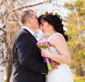 Loving groom kissing bride's forehead on wedding walk Royalty Free Stock Photo