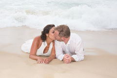 Loving groom kissing bride's mouth on beach Royalty Free Stock Images