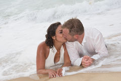 Loving groom kissing bride's mouth on beach Stock Photography