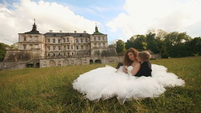 Loving groom kissing his beautiful bride's neck while both sitting on green lawn. Magnificent antique castle under blue stock footage