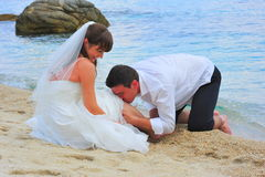 Loving groom kissing with passion his bride's leg Royalty Free Stock Image