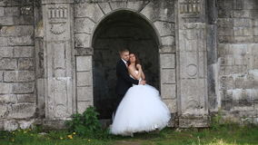Loving groom tenderly kisses his beautiful bride while embracing her standing in antique wall arch stock video footage