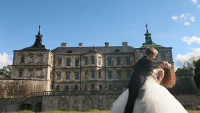Loving groom tilts his beautiful bride and kissing her in neck. Magnificent antique castle under blue sky with small stock video footage