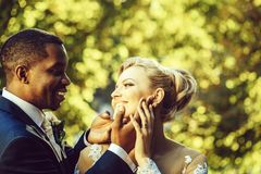 Loving groom touches face of adorable bride. Loving groom or african American men gently touches face of pretty girl or adorable bride with beautiful make up and stock photo