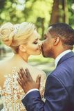 Loving groom touches shoulder of adorable bride. Loving groom or african American men gently touches shoulder of pretty girl or adorable bride, beautiful blond stock photography
