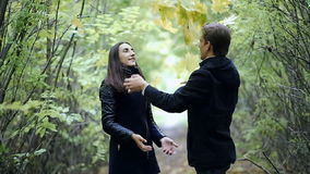 Loving guy and girl throwing leaves stock video footage