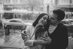 Loving guy hugs his beautiful happy girlfriend sitting on the windowsill in a cozy cafe. Black and white photo stock images