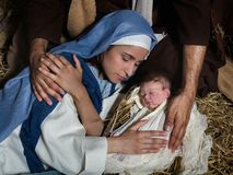 Loving hands in nativity scene. Live Christmas nativity scene in an old barn - Reenactment play with authentic costumes. The baby is a property released doll stock image