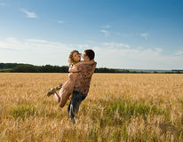 Loving happy couple on field Stock Images
