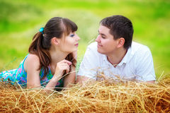 Loving happy couple having fun in a field on a haystack. Summer Royalty Free Stock Photos