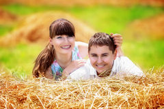 Loving happy couple having fun in a field on a haystack. Summer Royalty Free Stock Image