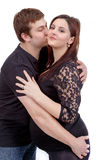 Loving happy couple, husband kissing pregnant woman Royalty Free Stock Image