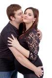Loving happy couple, husband kissing pregnant woman Royalty Free Stock Image