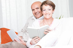 Loving happy couple relaxing reading at home Stock Image
