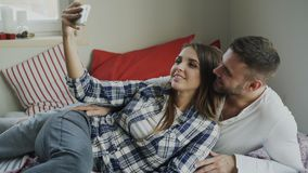 Married happy couple taking selfie portrain while lying on bed at home in the morning stock photo