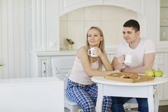Loving happy couple in their pajamas eating breakfast in the kit. Loving happy couple in their pajamas in the morning eating breakfast in the kitchen Stock Image