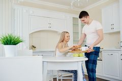 Loving happy couple in their pajamas eating breakfast in the kit. Loving happy couple in their pajamas in the morning eating breakfast in the kitchen Stock Photo