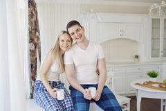 Loving happy couple in their pajamas eating breakfast in the kit. Loving happy couple in their pajamas in the morning eating breakfast in the kitchen Stock Images