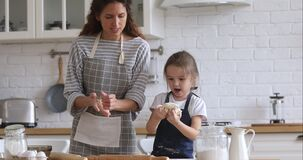 Happy mom teaching kid daughter kneading dough in kitchen together