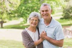 Loving happy senior couple holding hands at park Stock Photos