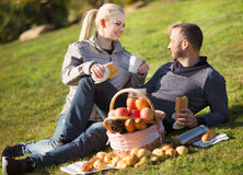 Loving happy young couple chatting as having picnic Royalty Free Stock Photography