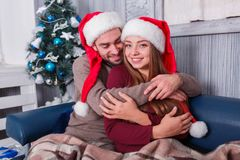 A loving and happy couple gently embrace while sitting on a sofa. Indoors. Stock Image