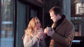 Loving heterosexual couple drinking hot tea outdoors in winter. Winter couple smiling happy in Valentine`s day. Beautiful young couple at backyard of their house stock video footage