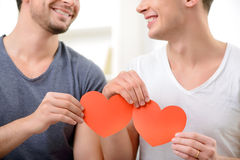 Loving homosexuals sitting on the sofa royalty free stock photos