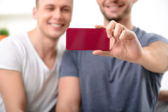 Loving homosexuals sitting on the sofa stock images