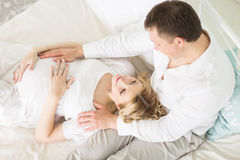 Loving husband and his pregnant wife on the bed. In the bedroom Royalty Free Stock Photo