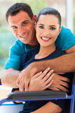 Loving handicapped couple. Loving husband hugging handicapped wife at home Royalty Free Stock Images