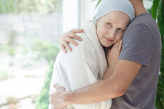 Husband hugging woman with cancer. Loving husband hugging hopeful women with cancer after successful chemotherapy Stock Photography