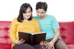 Loving husband reading together with pregnant wife. Isolated over white background royalty free stock photo