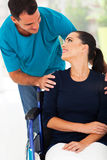 Husband handicapped wife. Loving husband talking to handicapped wife at home Stock Photography