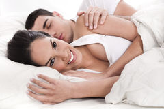 Loving husband and wife lying in bed Royalty Free Stock Photos