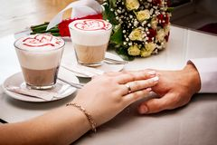 Loving husband and women touch each other hands. Coffee in a cafe for Valentine`s Day royalty free stock image
