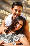 Loving Indian Couple. Happy Indian couple in American clothing sitting steps and holding each other Stock Images