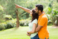 Loving indian couple. Loving young indian couple looking and pointing in the forest Royalty Free Stock Photos