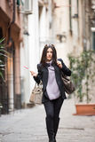 Loving Italy. A young beautiful dark hair woman with a handbag walking with intent in the beautiful narrow streets of Genoa, an old Italian harbor city royalty free stock photo