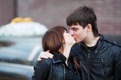 Happy young fashion couple in love kissing outdoor Stock Images