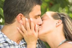 Loving kiss. Young couple in love kissing in the garden Stock Photos